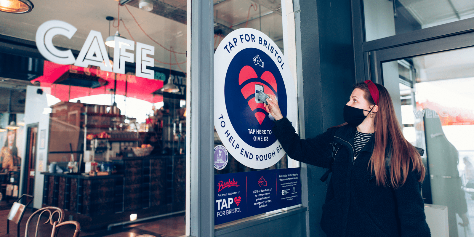 Woman tapping her credit card at a charity point on a bar window